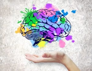 Image: Hand holding colorful brain sketch on concrete background.