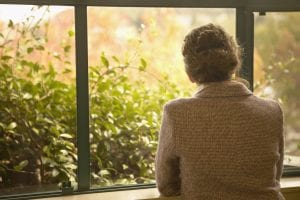 Image: Rear view of woman looking out window