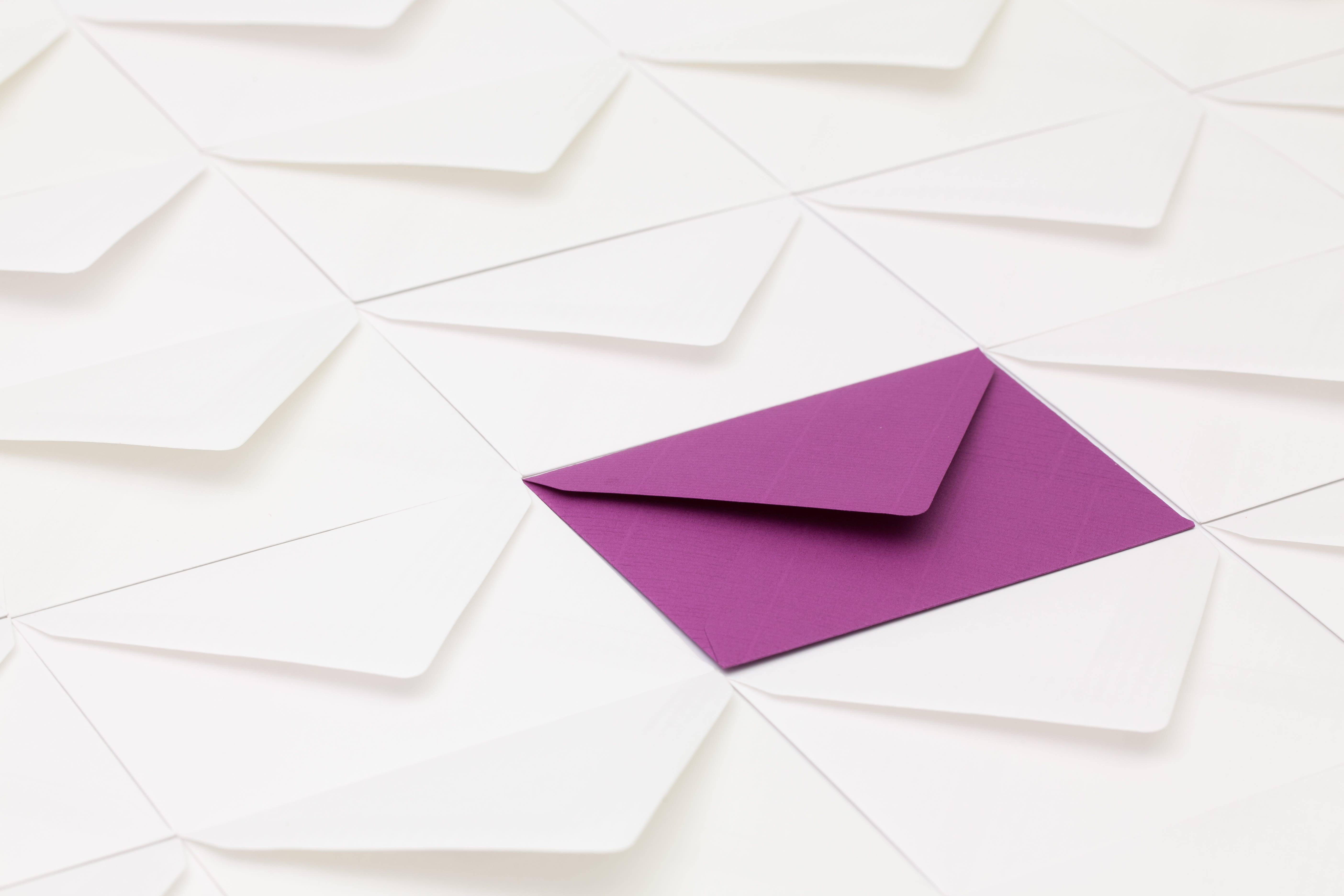 Composition with white envelopes and one purple envelope on the table.